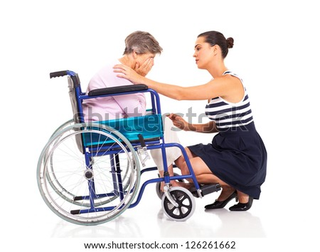 young woman comforting disabled senior mother on white - stock photo