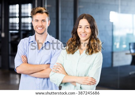 Young woman communicating on mobile phone in front of conference room in office - stock photo