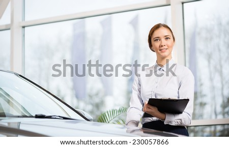 Young woman consultant in show room standing near car - stock photo
