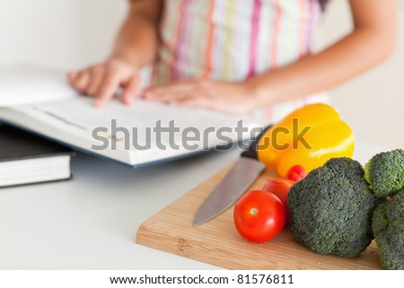 Young woman consulting a notebook while standing in the kitchen