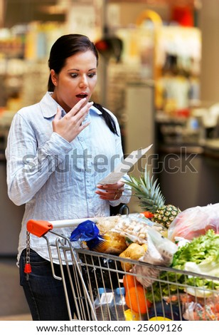Young woman controls a bill of sale in supermarkets - stock photo