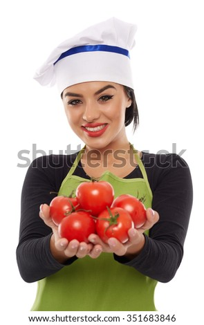 Young woman cook in apron offering a bunch of freshly picked tomatoes - stock photo