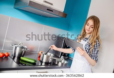 Young woman cooking and tasting dinner in the kitchen. Reading recipe from tablet