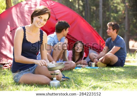 Young Woman Cooking Breakfast For Friends On Camping Holiday