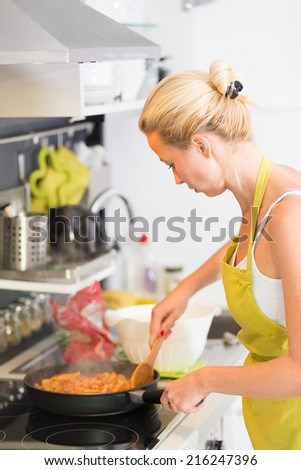 Young Woman Cooking Healthy Mediterranean Pasta with tuna fish. Fast, easy and delicious recipe. - stock photo