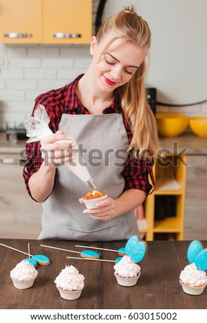 Girl makes easter biscuit cake kitchen stock photo 604431164 young woman cooking homemade cup cakes in kitchen culinary masterpiece gift small business negle Images