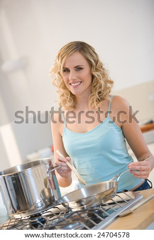 young woman cooking in a kitchen - stock photo