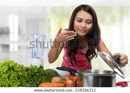 Young Woman Cooking in the kitchen. Healthy Food Diet. Cooking At Home. Prepare Food - stock photo