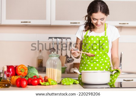 Young Woman Cooking in the kitchen. Healthy Food. Dieting Concept. Healthy Lifestyle. Cooking At Home. Prepare Food - stock photo