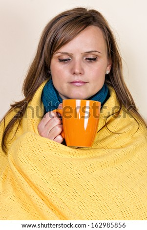 Young woman covered with a blanket, holding a cup of tea, sitting on couch at home - stock photo