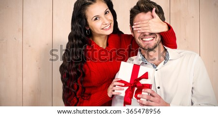 Young woman covering eyes of partner holding gift against wooden planks - stock photo