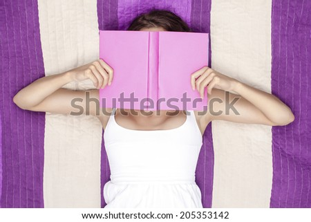 Young woman covering face with book while lying on picnic blanket - stock photo