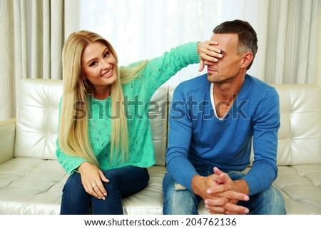 Young woman covering her boyfriend`s eyes