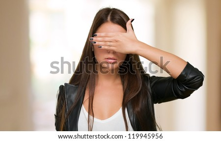 Young Woman Covering Her Eyes against an abstract background - stock photo