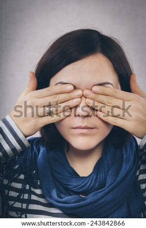 young woman covering her eyes with hands - stock photo