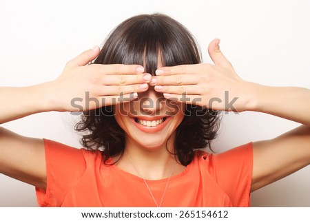 Young woman covering her eyes with her hands.Studio shot. - stock photo