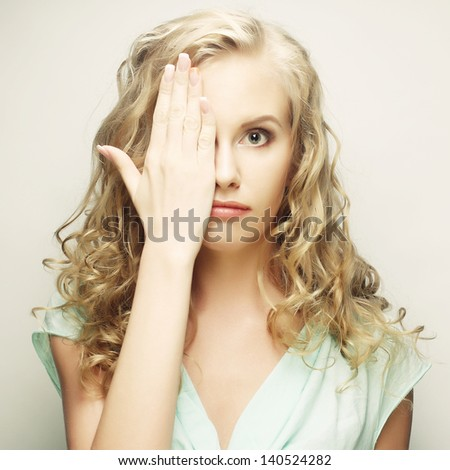 young woman covering her eyes with her hands. Studio shot agains - stock photo