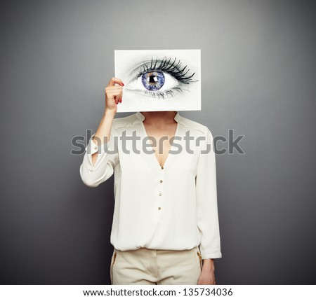 young woman covering image with big eye. concept photo over grey background