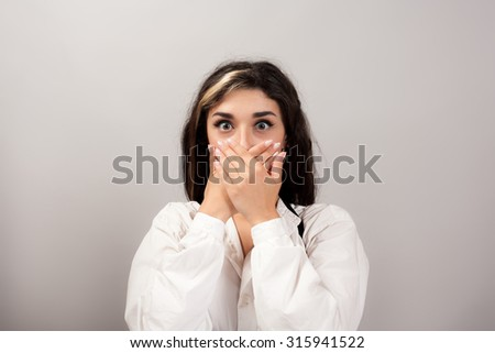 Young woman covering mouth with her hand - stock photo