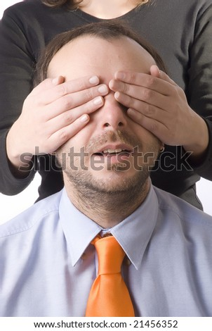 young woman covering the eyes of a business man
