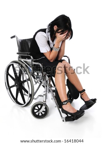 Young woman crying sitting on a wheelchair - stock photo