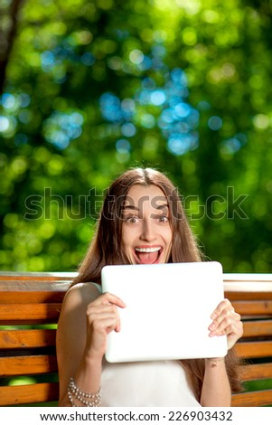 Young woman crying using social networking having a lot of friends sitting on the bech at the park - stock photo