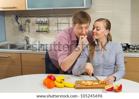 Young woman cutting banana with her boyfriend on kitchen - stock photo