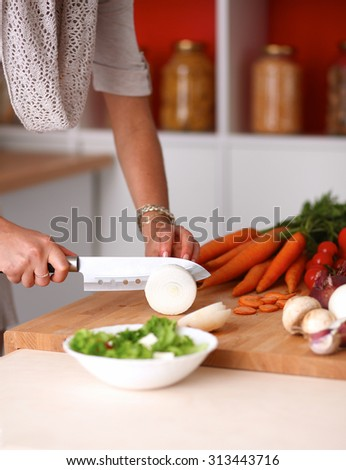Young woman cutting vegetables in the kitchen