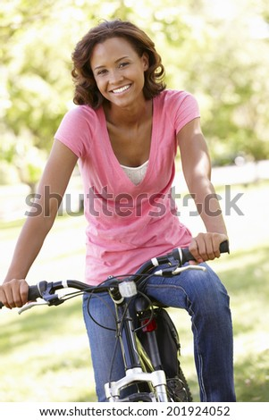 Young  woman cycling in park - stock photo