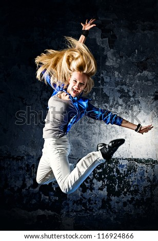 Young woman dancer jumping. At wall background. - stock photo