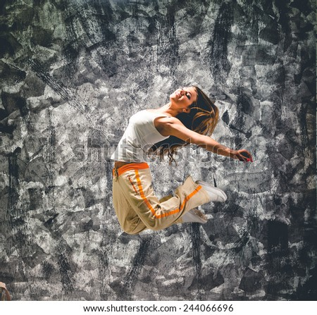 Young woman dancer jumping. On grunge wall background. - stock photo