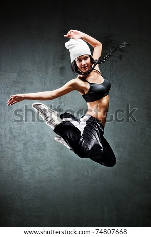 Young woman dancer jumping. On wall background. - stock photo