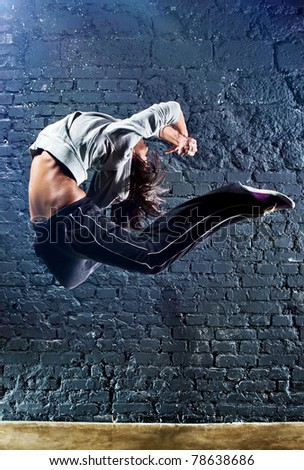 Young woman dancer jumping. On wall background.