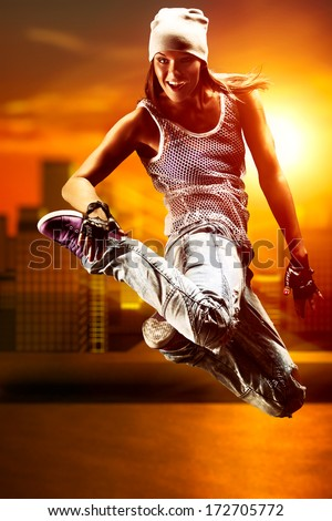 Young woman dancer on city background.