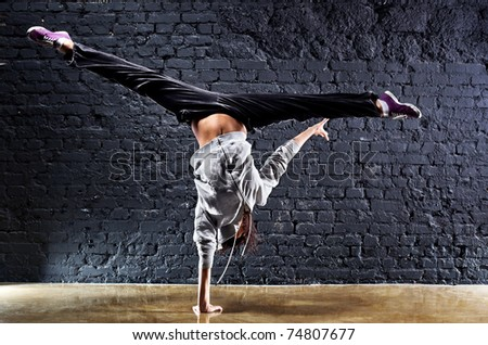 Young woman dancer on wall background. Contrast colors. - stock photo