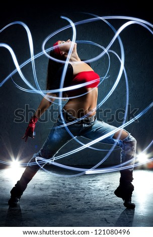 Young woman dancer with lights traces.