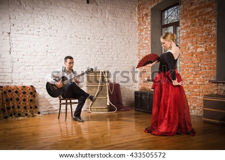 Young woman dancing flamenco in traditional flamenco dress with fan and a man playing the guitar