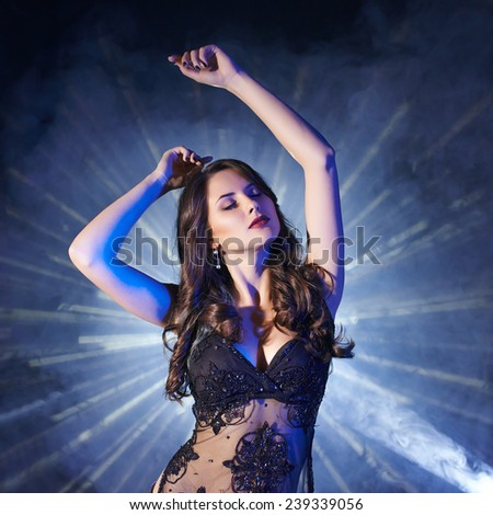 Young woman dancing in club with light rays on background - stock photo