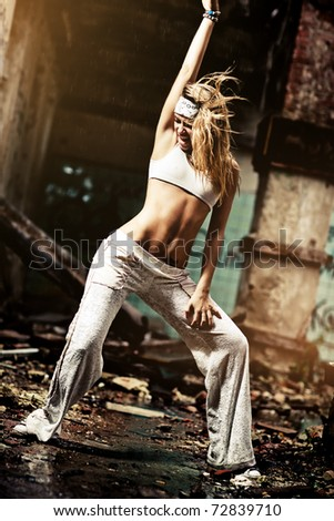 Young woman dancing on industrial background. Contrast colors.