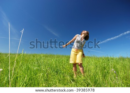 Young woman dancing on the green field