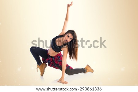 Young woman dancing street dance over ocher background - stock photo