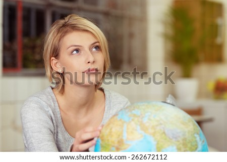 Young woman daydreaming about her summer vacation as she sits touching a world globe staring up thoughtfully into the air - stock photo