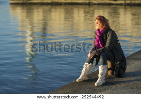 Young woman daydreaming and enjoying the peaceful sunset at the harbour. - stock photo