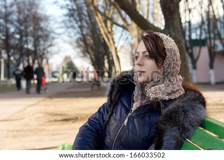 Young woman daydreaming on a park bench sitting staring into the distance with a faraway expression wearing a headscarf and warm winter fashion - stock photo