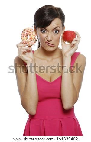 Young woman deciding between an apple or doughnut. - stock photo