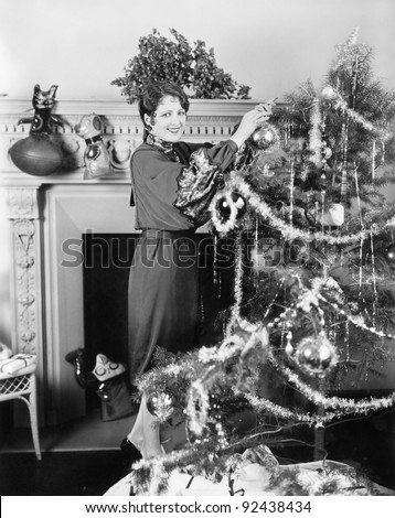 Young woman decorating a Christmas tree
