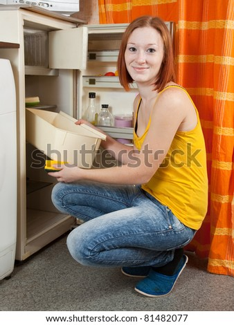 Young woman  defrosting the refrigerator at her kitchen - stock photo