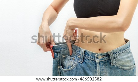 Young woman delighted with her dieting results on white background, A slim woman is showing how much weight she lost, healthy concept, healthcare content and selective focus.