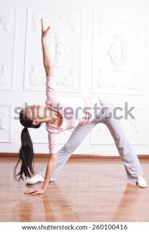young woman demonstrating advanced yoga posture, in an empty room with natural light.