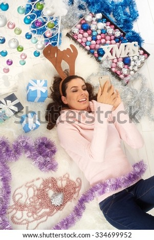 Young woman dialing on mobilephone, lying on floor surrounded by christmas decoration. - stock photo